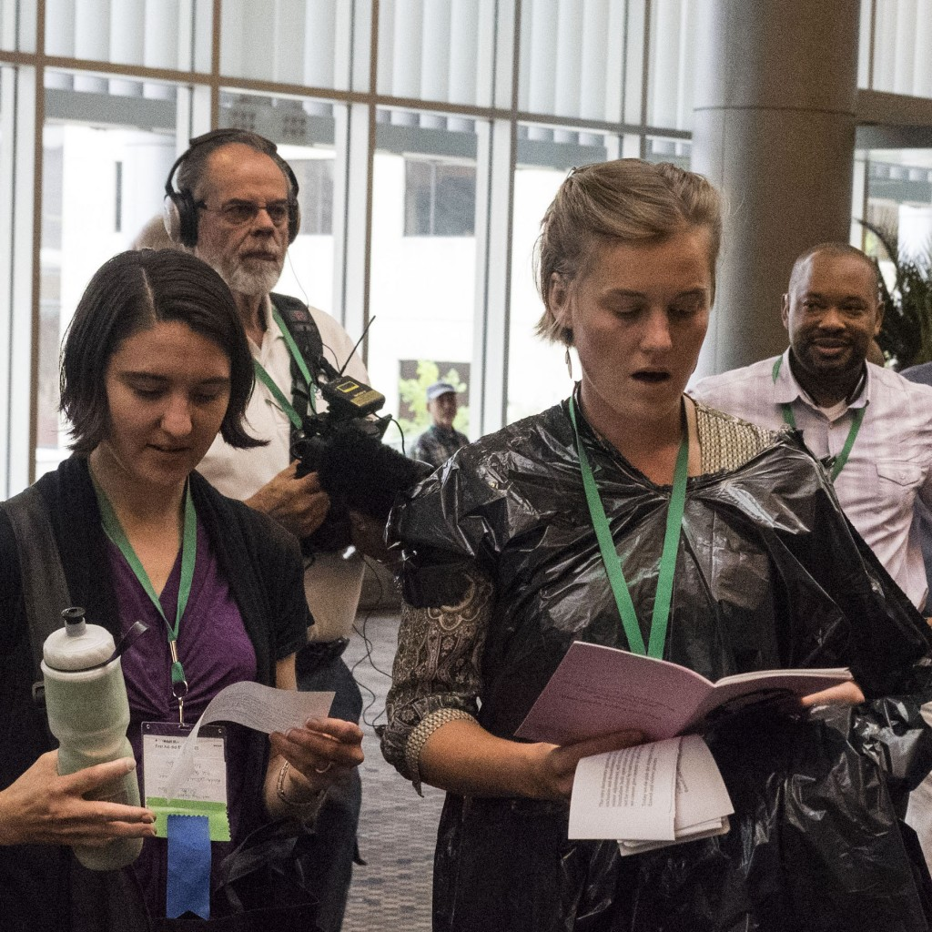 Members of the Mennonite USA wear garbage bags during the hymn sing outside the delegate assembly, symbolizing the de-pinking of the delegate assembly, a visual representation of the silencing LGBTQ community.